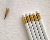 white pencils with a gold foil flamingo