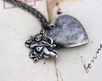 cupid. locket necklace. silver ox with etched lines heart