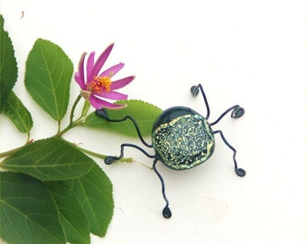 Fused dichroic glass bug with a sparkly yellow and black back