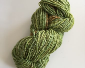 Handspun wool/silk/alpaca blended and plyed yarn color green with a bit of gold at the end.