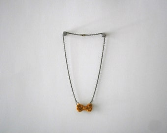 Necklace with tiny knit bow in golden yellow
