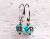 Handwoven matte turquoise glass bead earrings with deep orange folk art daisy, oxidised sterling loops - Songbead UK, narrative jewelry
