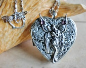 Music box locket,  heart shaped locket with music box inside, in  silvertone with fairy.