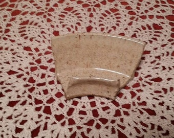 Small ceramic draining soap dish for shower.