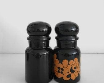 a pair of black Bengium milkglass bottles