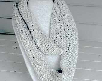 Knitted infinity scarf with a blend of gray and white.  Fits all sizes and long enough to wrap around your neck