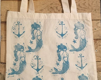 Hand printed tote bag, with candland Studios Mermaid and anchor Lino print design in blue.