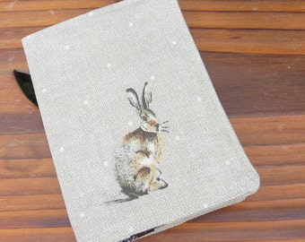 A fabric passport sleeve with a whimsical hare design.  Travel.