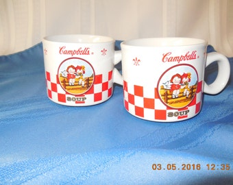 A pair of Campbell's soup mugs with the two Campbell's soup kids on the front.