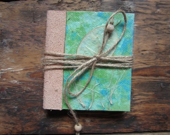 Bound journal made out of  recycled handmade paper with leather backing, decorated with raw nature materials.
