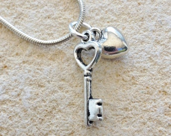 Silver key necklace with heart charm on silver snake chain
