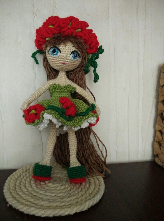 Doll. Toy handmade. Amigurumi. Doll with flowers. Knitted toy.