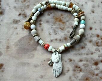 Hamsa Talisman Collier w/ Lampwork, Porcelain, Stoneware, Antique White Greenheart, Kutschi Bell, African Bronze, Mala Yakbone, & Buckskin
