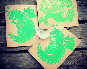 Set of 3 mythical creature block print cards in green ink on brown cardstock. 3 blank cards and envelopes. Dragons and mermaid.