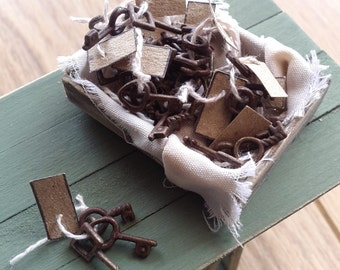 1/12th scale aged old crate filled with rusty old sets of keys with string