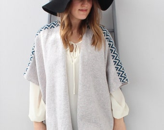Knitted lambswool grey drape cardigan with blue and cream geometric stripe. The perfect shawl/ cape to have this winter.