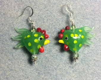Green with yellow spots lampwork heart shaped rooster bead earrings adorned with green Czech glass beads.