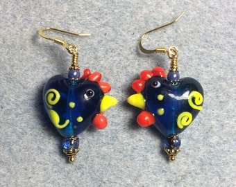 Transparent blue with yellow squiggles heart shaped lampwork hen bead earrings adorned with blue Czech glass beads.