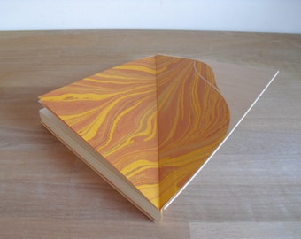 Triangle notebook, with wooden cover and yellow spine.