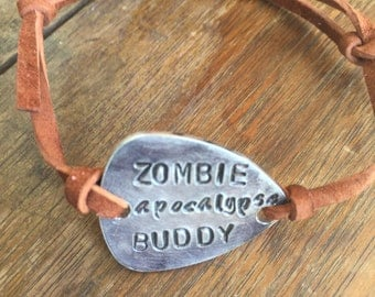 """Zombie Apocalypse Buddy - Distressed Copper Guitar Pick Hand Stamped Bracelet Natural Medium Brown Leather Cord Adjustable 6"""""""