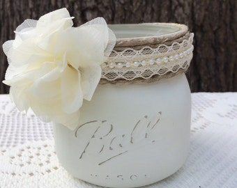 Eggshell colored distressd mason jar with twine and flower