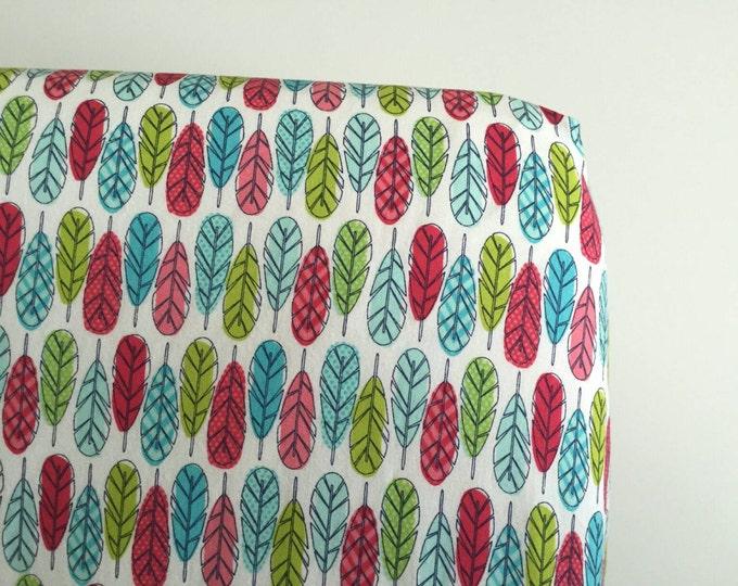 Pink green and blue feathers fitted crib sheet