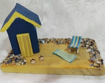 Handmade miniature beach hut with real shingle and hand crafted deckchair and flip flops made using pyrography.