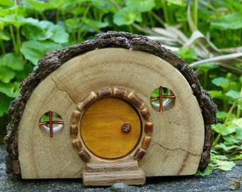 Rustic Wooden Hobbit house with Bark Roof and Yellow Door
