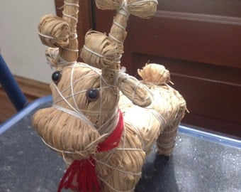 Straw reindeer with bright red ribbons