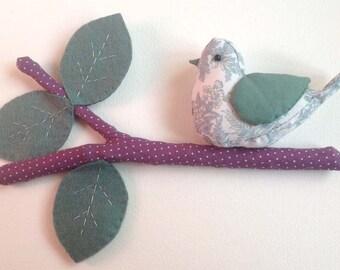 Teal bird on a purple branch