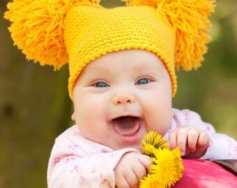 Yellow hat with pom poms