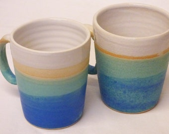 Set of two white and turquoise blue dipped mugs.