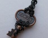 SECRET key pendant -- wire wrapped antiqued copper replica key, black wire, engraved antique copper