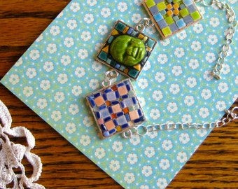 Bracelet made with Tiny Tiles, Center Tile with Happy Green Porcelain Baby Face. Three large links. Greens, Yellows, Orange, Coral, Cobalt.
