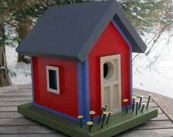 Red Birdhouse with Blue Trim, Yellow Flowers