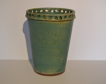 Turquoise green/blue vase with teardrop piercing at the rim.