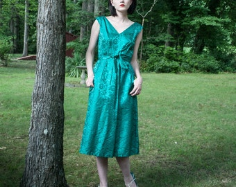 1950s . emerald green phoenix brocade dress with pockets . s