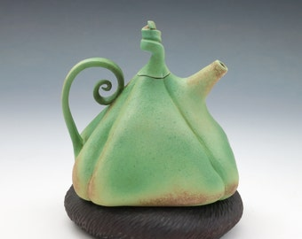 Puffy porcelain teapot in green & gold with brown pillow