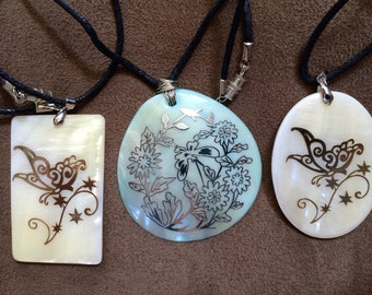 lot of three shell pendants with foil design on cloth necklace sold as is