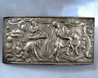 Cloak clasp/brooch. antique.  Oblong, a classical Greek scene with 3 people, pressed pewter with a slight curve, quite heavy.  c 19th. cent.