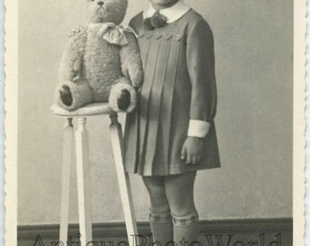 Cute girl posing with toy teddy bear on stool antique photo