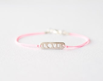 Neon pink cord bracelet with silver love sign