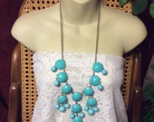 Turquoise colored acrylic cabochons in silver metal discs bib necklace.