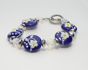Handmade blue, white , and yellow lampwork beaded bracelet embellished with swarovski crystals and sterling silver beads.