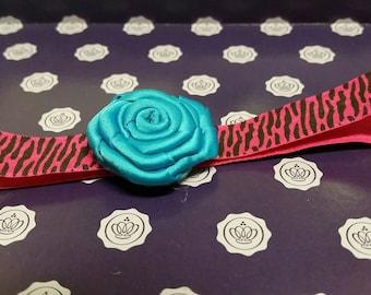 Pink zebra print headband with blue flower attached.