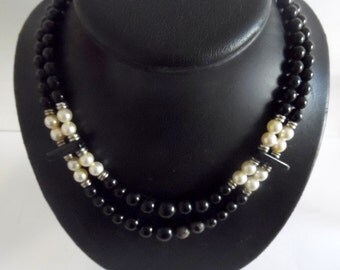 Pretty choker style necklace, made of black beads, and accented with pearls