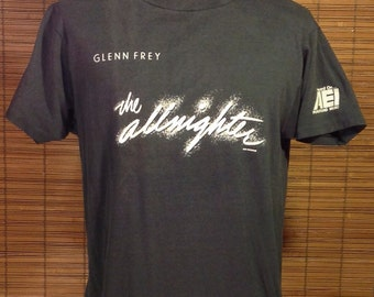 "Vintage 1984 Large 42-44 Glenn Frey ""the allnighter"" Concert Souvenir T-shirt. ""Heard On AEI Foreground Music"". Black Hanes Fifty-Fifty bran"