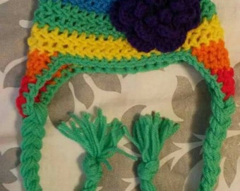 Rainbow earflap hat with braids and flower.