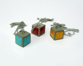 Hanging square of concrete in various colors. Necklace of cement.