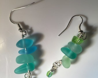Different shades of light blue and green seaglass wire wrapped with tiny blue-green bead hanging from them on sterling silver earwires.